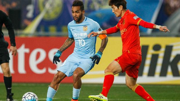 Kim Jae-Sung competes for the ball with Jiangsu striker Alex Teixeira.
