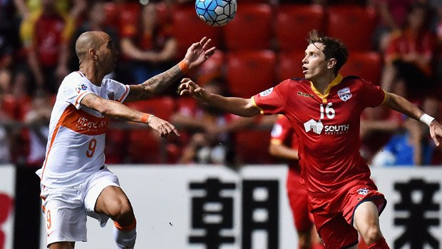 Reds winger Craig Goodwin challenges for the ball with Shandong star Diego Tardelli.
