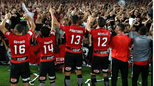 Wanderers players celebrate their Sydney Derby win with their fans at ANZ Stadium on Saturday night.