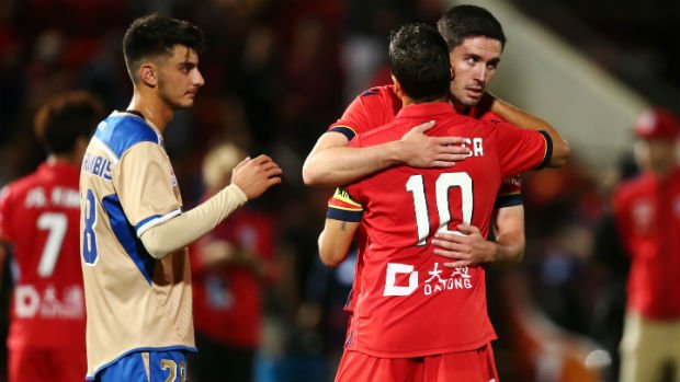 Reds defender Dylan McGowan congratulates Marcelo Carrusca after he coverts a second-half penalty.