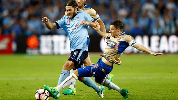 Sydney FC midfielder Josh Brillante looks to avoid the challenge of a Jets defender at Allianz Stadium.