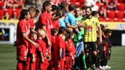Adelaide United and Wellington Phoenix players shake hands before kick-off at Coopers Stadium on Sunday.