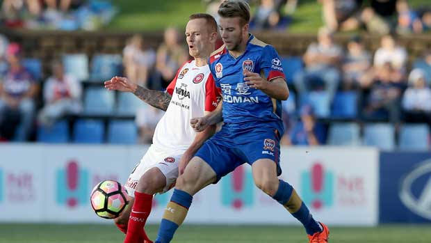 Newcastle Jets winger Andrew Hoole battles for the ball with the Wanderers' Jack Clisby.