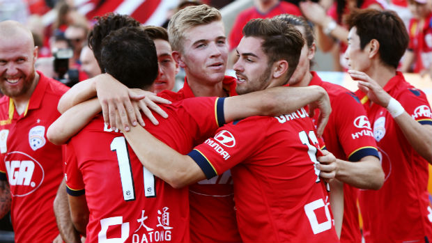 Adelaide United players celebrate their late winner against Brisbane at Coopers Stadium on Sunday.