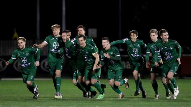 Bentleigh Greens players celebrate after Lambros Honos slots the winning penalty against Hume City.