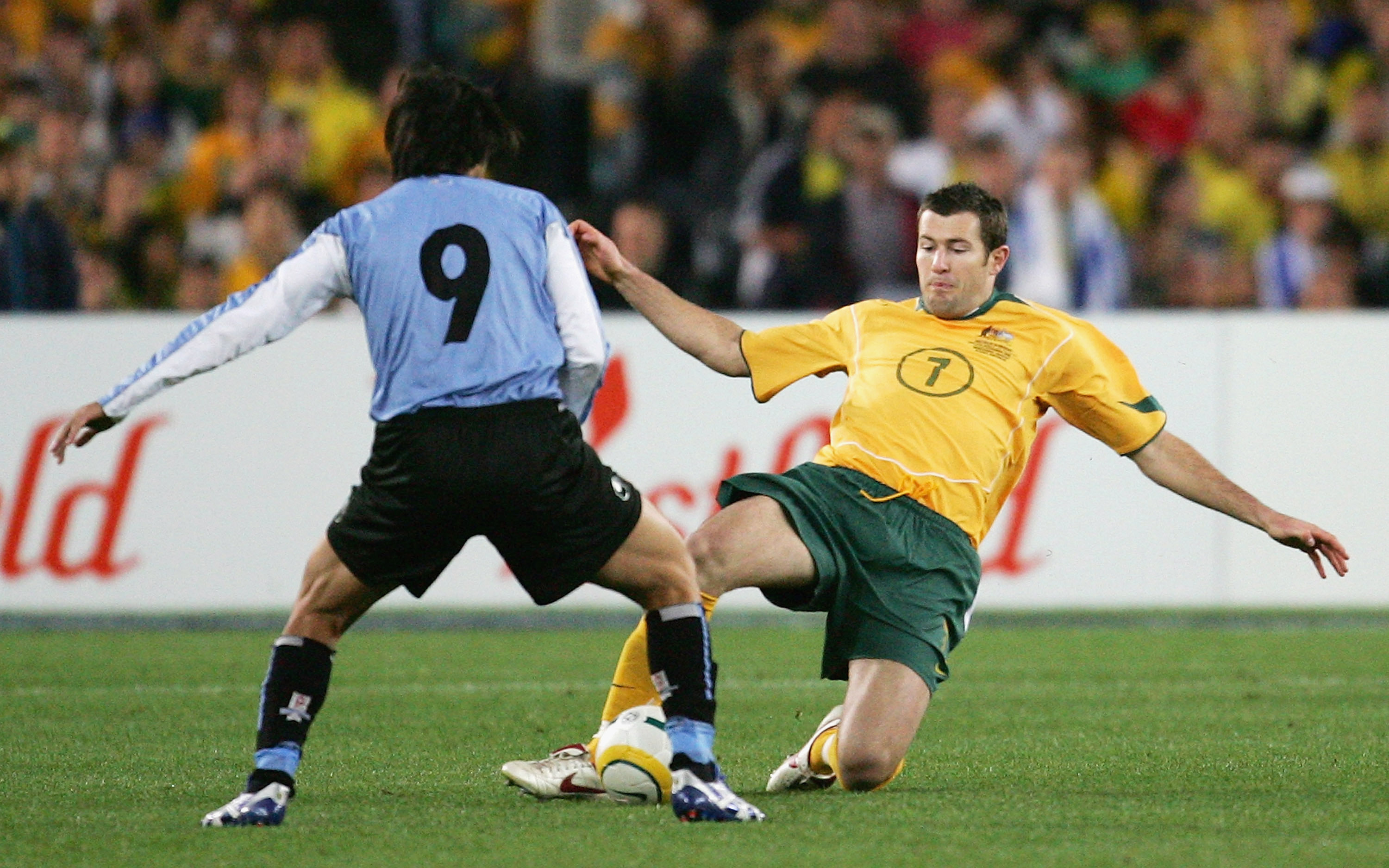 The tireless Brett Emerton challenges for the ball with Uruguay's mercurial playmaker Alvaro Recoba.