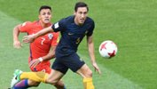 Mark Milligan gets to the ball ahead of Chile's Alexis Sanchez.
