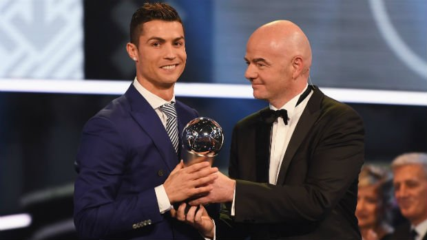 Cristiano Ronaldo accepts his World Player of the Year award from FIFA President Gianni Infantino.