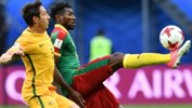 Mark Milligan fights for the ball with Cameroon's Andre Zambo.