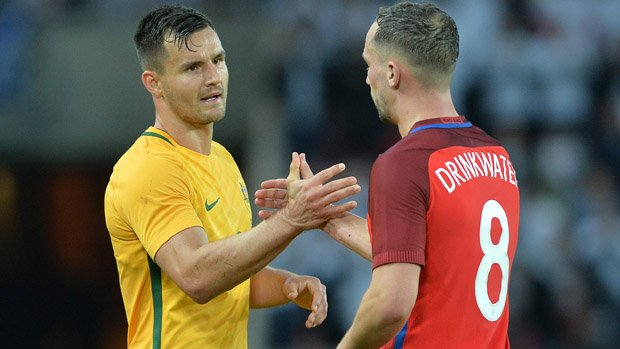 Bailey Wright shakes hands with England midfielder Danny Drinkwater.
