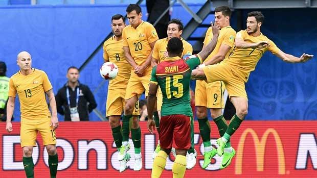 The Australian wall does its job to block a Cameroon free-kick.