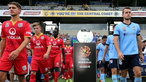 Adelaide United and Sydney FC players walk onto the field in Gosford for last season's Foxtel NYL Grand Final.