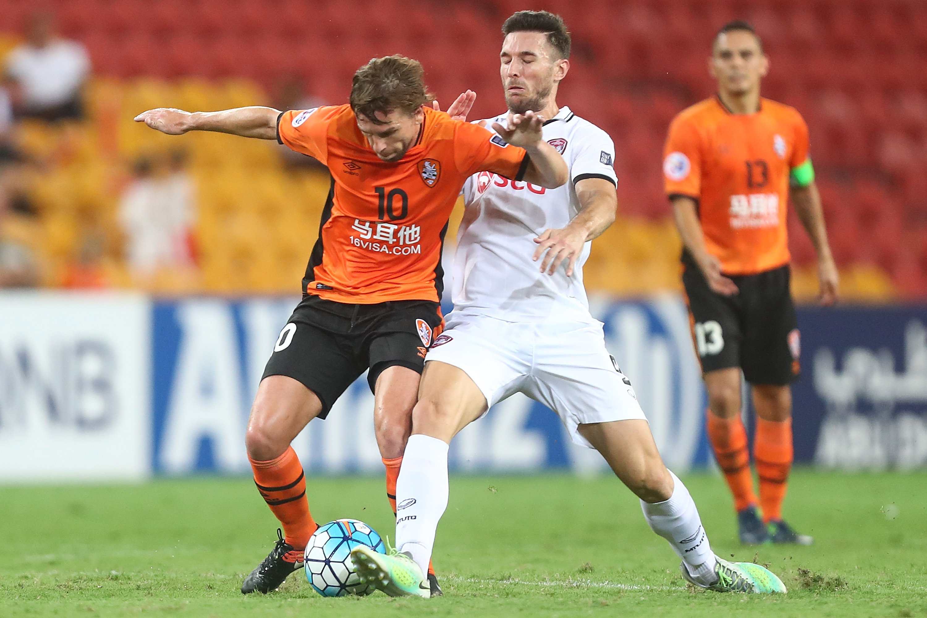 Brett Holman of the Roar and Xisco Jimenez of Muangthong United compete for the ball during the AFC Champions League match between the Brisbane Roar and Muangthong United at Suncorp Stadium on February 21, 2017 in Brisbane, Australia.