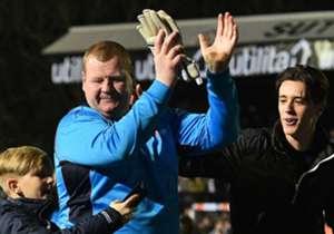 """Il 45enne portiere di riserva del Sutton United Wayne Shaw è stato sorpreso in diretta TV mentre addentava di gusto un panino in panchina. La sua figura non esattamente filiforme ha fatto il giro del mondo diventando il simbolo dei tanti """"atleti della ..."""