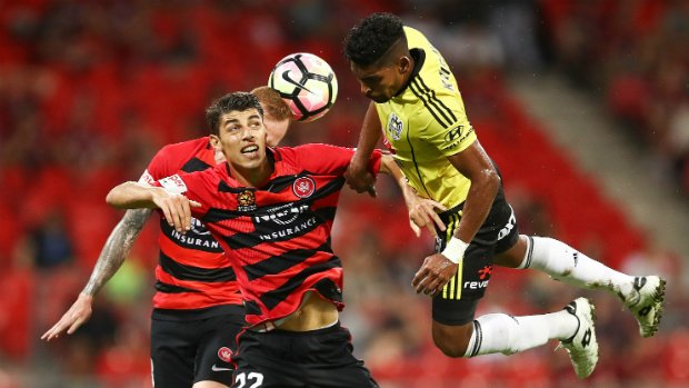 Roy Krishna is well marshalled by two Wanderers defenders.