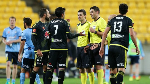 Wellington Phoenix players seek clarification from referee Shaun Evans as to why he blew full-time before a final incident could be fully reviewed.