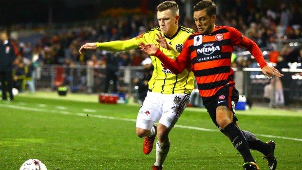 Phoenix's Scott Galloway fights for possession with Western Sydney Wanderers' Josh Risdon.