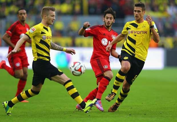 Leverkusens Calhanoglu im Dreikampf mit den Dortmundern Reus und Kehl