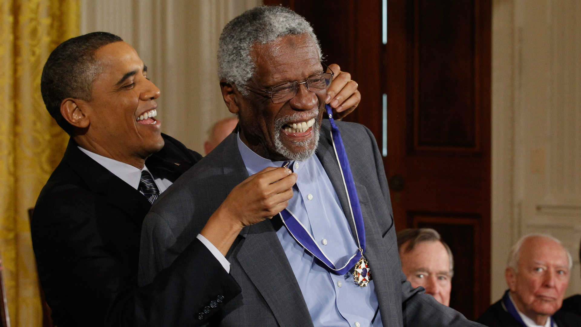photo shows bill russell kneeling with presidential medal
