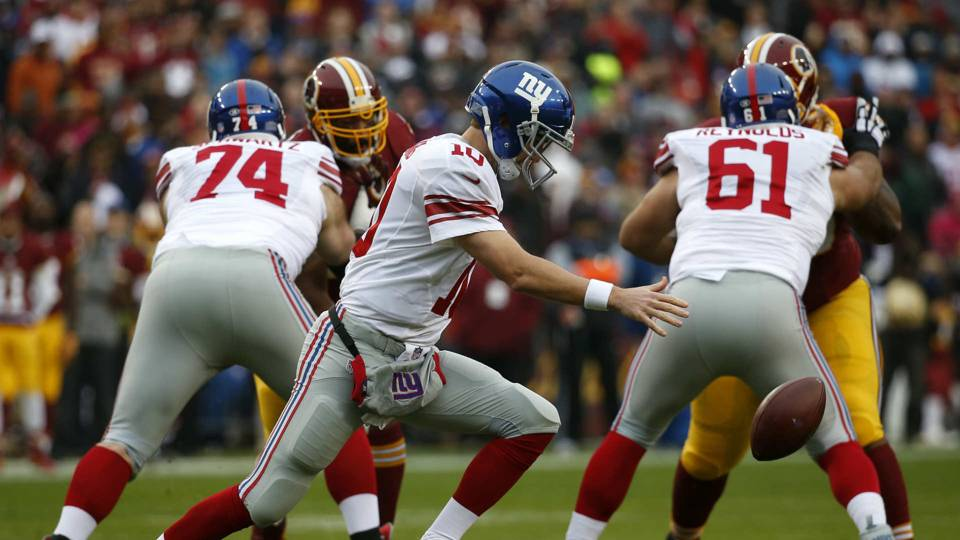 Eli Manning fumbles with Geoff Schwartz (74) and Dallas Reynolds (61) blocking.