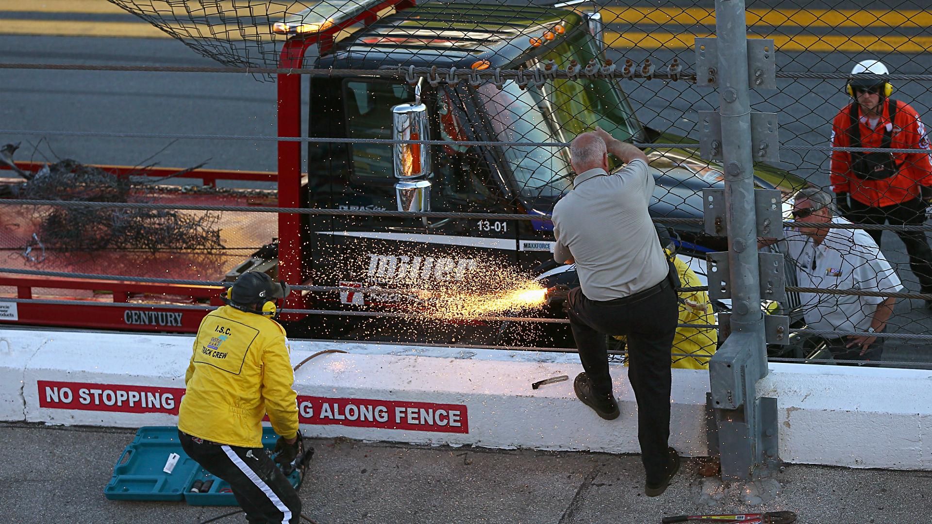 Track officials work on damage to the SAFER barrier