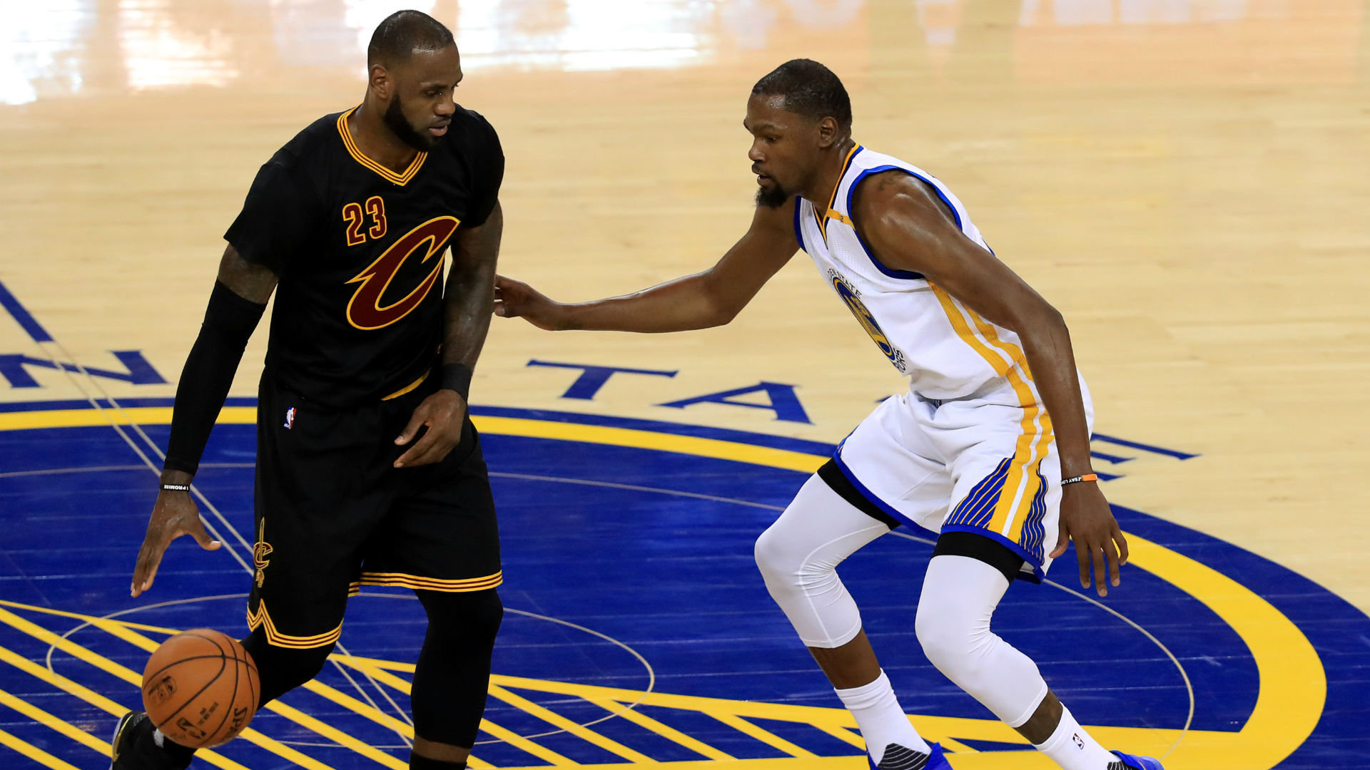 Cavs forward Le Bron James defended by Warriors forward Kevin Durant