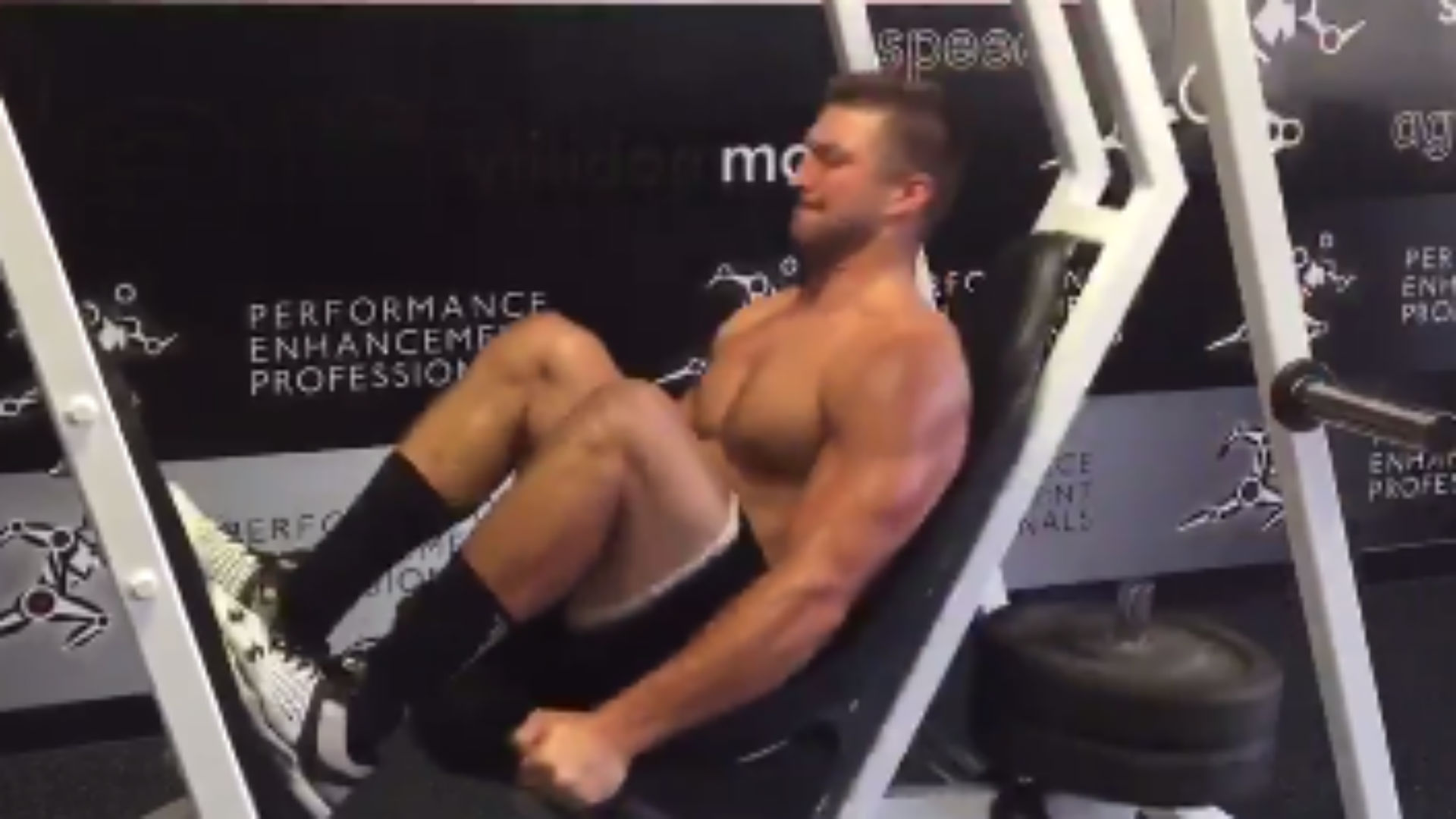 Tim Tebow does weird leg workout on a swing contraption