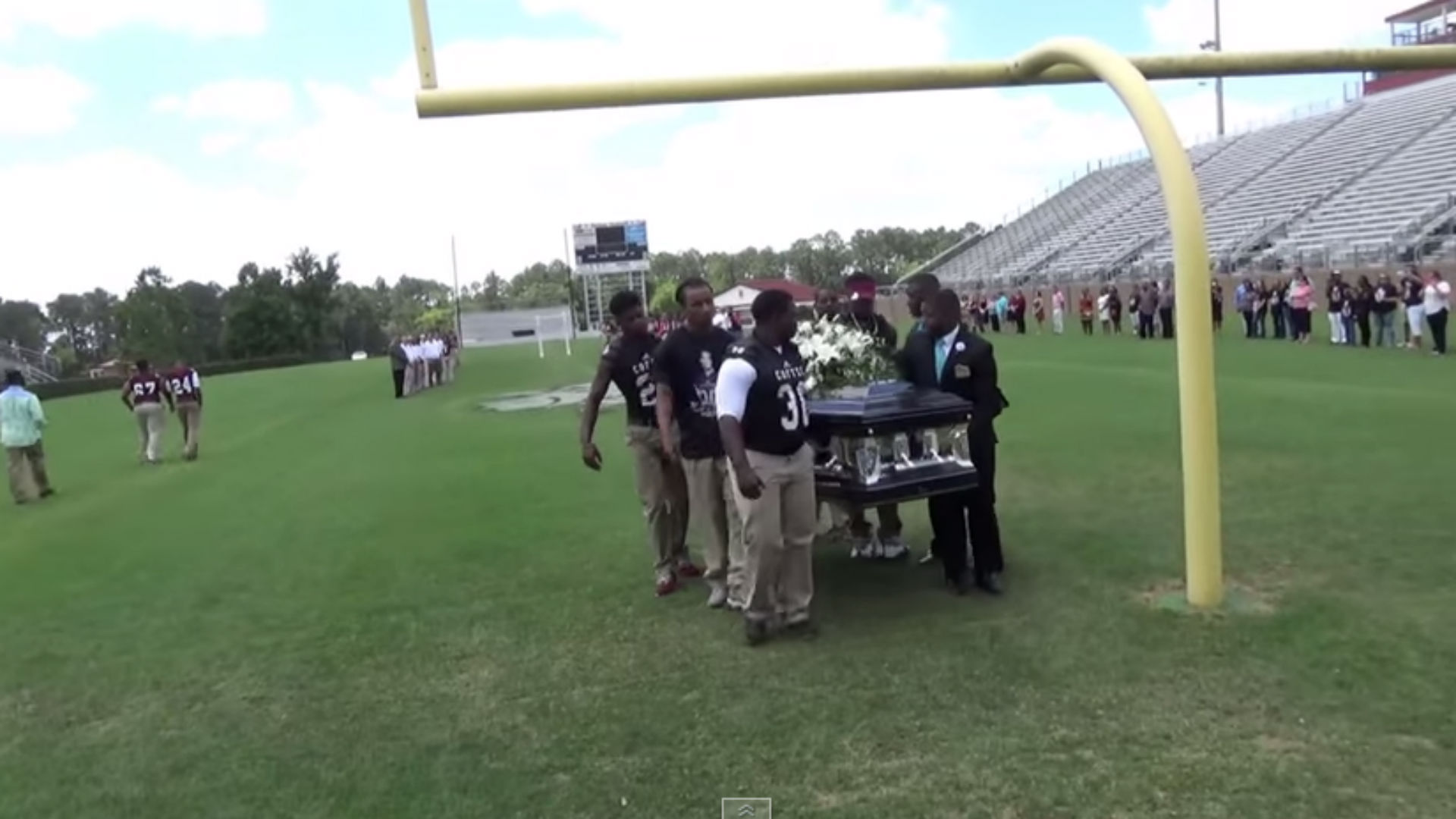 High school football team grants teammate's dying wish by carrying his casket across field