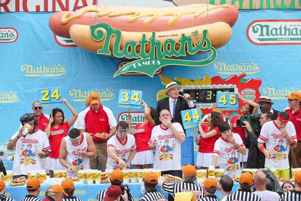 Defending champion eats 74 hot dogs to set new record