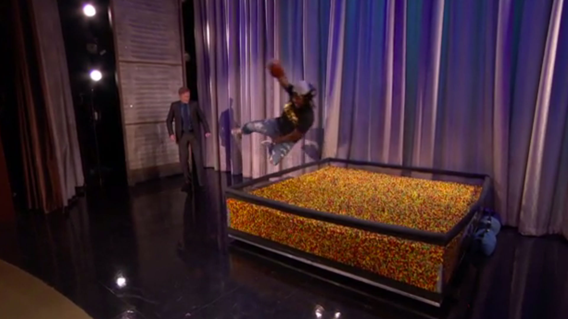 Marshawn Lynch dives into an end zone of Skittles on 'Conan'