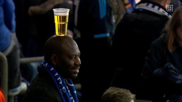 Schalke-Fan balanciert Bier auf dem Kopf