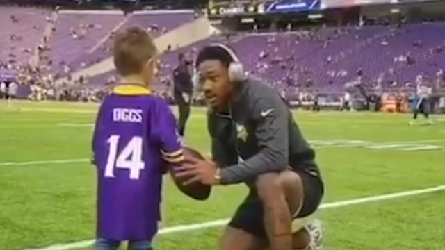 Stefon Diggs plays catch with a fan in a Diggs jersey before game