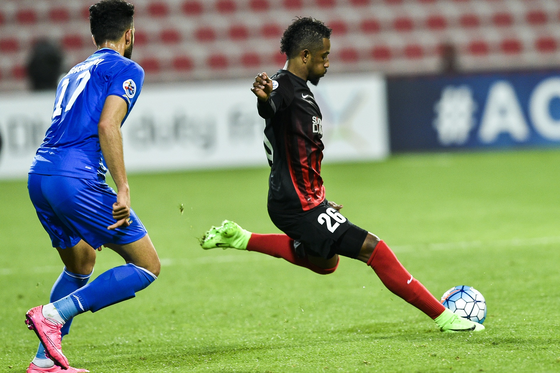 Abdulaziz Haikal (R) of UAE's Al-Ahli FC kicks the ball past Ali Ghorbani of Iran's Esteghlal FC