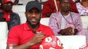 Jay Jay Okocha autographs footballs for fans