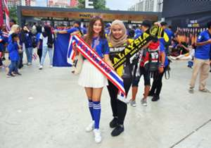 A Thailand fan and a Malaysia fan pose for a photo together just before the first leg semi-final match between the two teams, at the Bukit Jalil National Stadium.