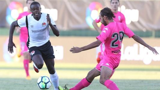Vincent Oburu challenges for the ball with Javi Soler