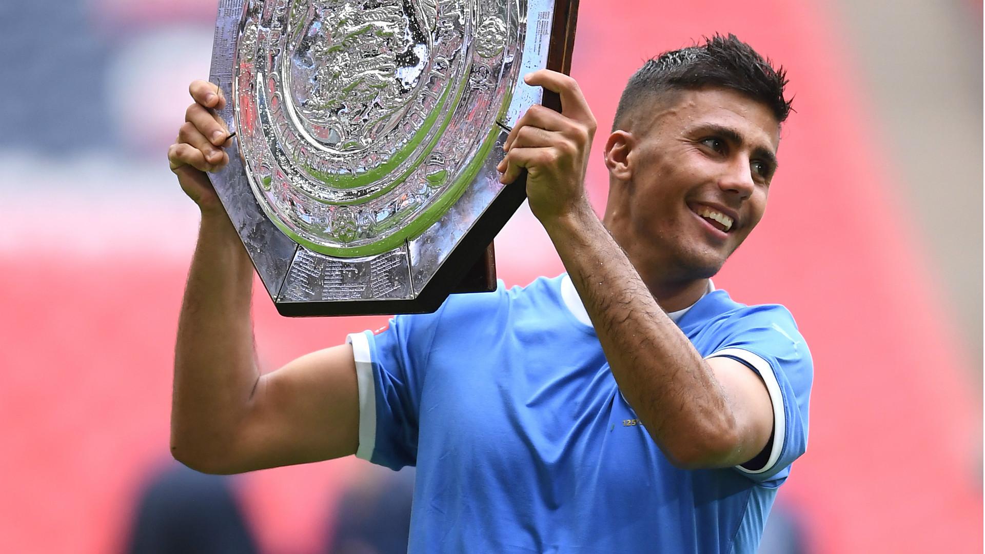 Man City midfielder Rodri holds aloft the Community Shield as City win it once more.