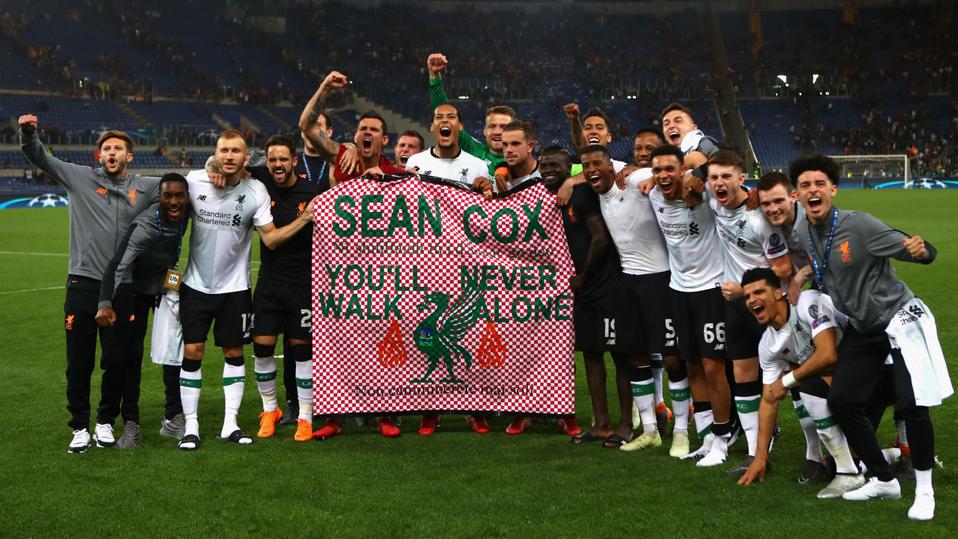 Liverpool players hold a banner in tribute to injured fan Sean Cox