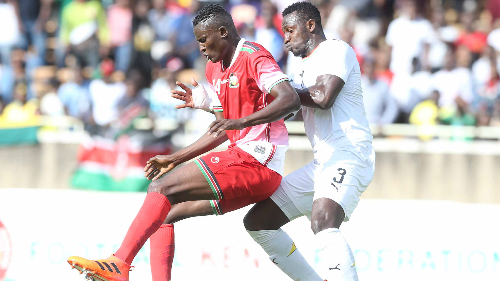 Michael Olunga of Kenya v Ghana defender.