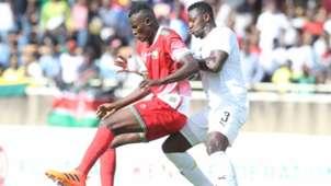 Michael Olunga of Kenya v Ghana defender.