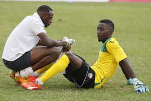 Harambee Stars goalkeeper Arnold Origi is consoled by keeper trainer Mathews Ottamax