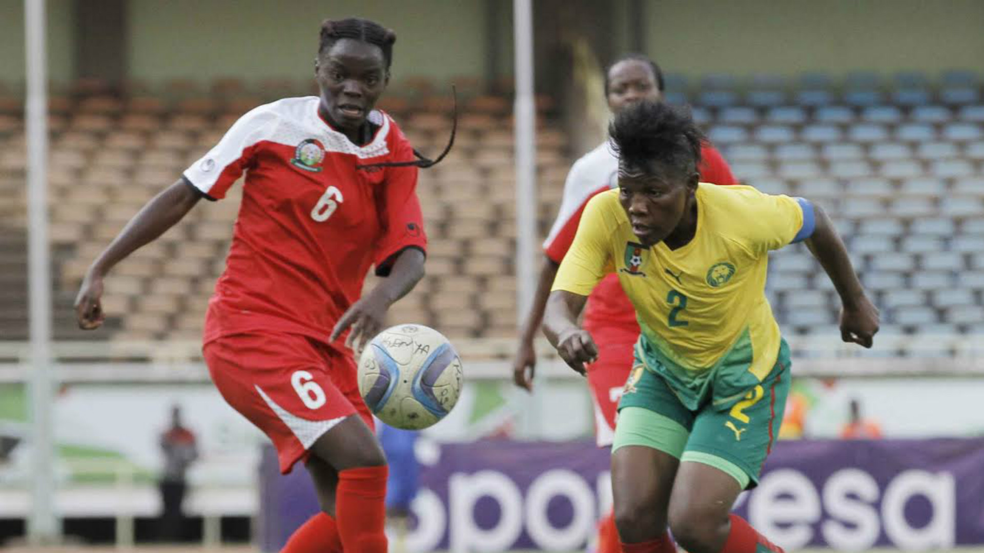 Caroylne Anyango of Harambee Starlets goes for the ball under challenge from a Cameroon opponent