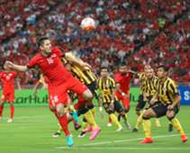 Singapore's Daniel Bennett winning a header againt Malaysia's Shahrul Saad