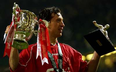 Liverpool's Robbie Fowler holds aloft The Worthington Cup and Man of the Match trophies