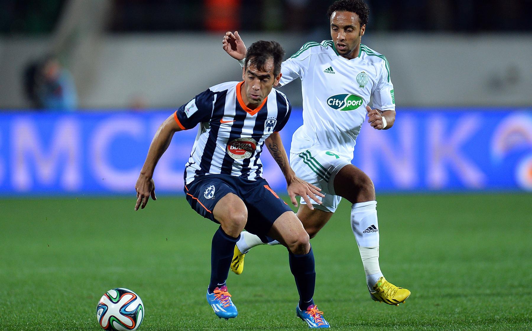 Cesar Delgado of Monterrey is challenged by Issam Erraki Raja Club World Cup 2013