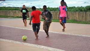 South African kids playing football by the beach