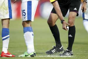 A referee uses vanishing spray during a football match