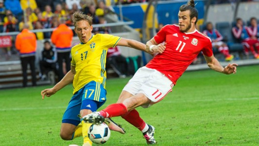 Wales' Gareth Bale and Sweden's Ludwig Augustinsson challenge for a 50-50 ball
