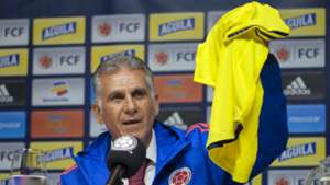 Carlos Queiroz holds up a Colombian jersey as he speaks during a press conference in Bogota 07022019