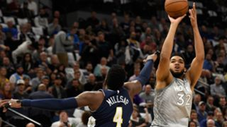 Karl-Anthony Towns shoots the ball over Paul Millsap